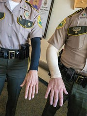 Two state troopers show off the agency provided tattoo cover-ups. Starting July 1 new applicants to the Vermont State Police can have tattoos visible on their forearms.