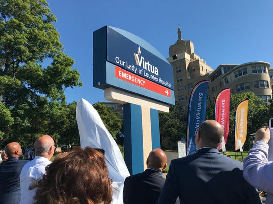 Beneath the hospital's limestone statue of Our Lady, onlookers cheer as a new sign is revealed at Virtua Our Lady of Lourdes Hospital in Camden on Monday.