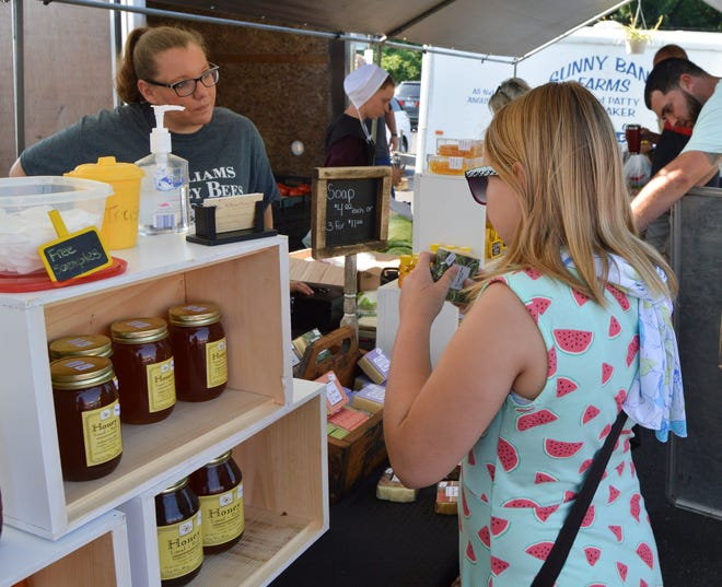 Courtney Williams speaks with customers at her booth, Williams Honey Bees, during the Chillicothe Farmers Market.
