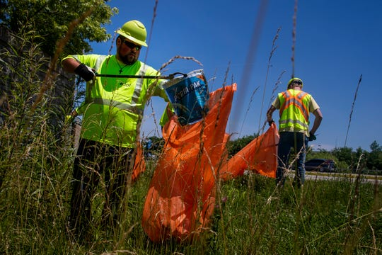 Shawn O'Rourke picks up trash alongside Interstate 275 in Batavia Wednesday, June 26, 2019. O'Rourke has worked for the Ohio Department of Transportation for two years.