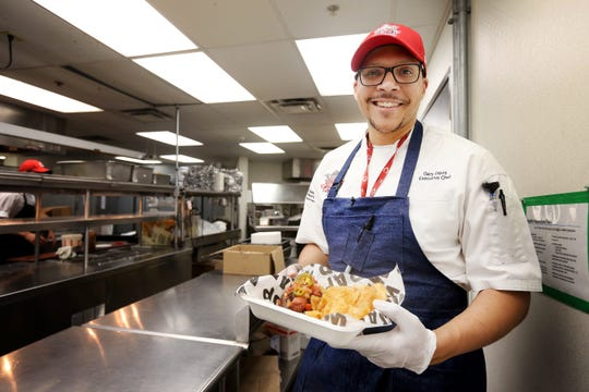 Executive Chef Gary Davis holds one of his signature hot dog dishes at Great American Ball Park. Davis has been executive chef since the 2018 season.