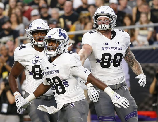 Jeremy Larkin of Northwestern (28) celebrates with teammates Cameron Green (84) and Trey Pugh (80) after his rushing touchdown at 7:58 in the first quarter against Purdue Thursday, August 30, 2018, in West Lafayette. Northwestern defeated Purdue 31-27.