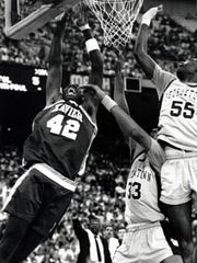 Xavier University big man Tyrone Hill (42) goes up to score against Georgetown in the second round of the 1990 NCAA Tournament at the RCA Dome in Indianapolis, Indiana. Xavier, the No. 6 seed, upset the No. 3 Hoyas to earn the Musketeers' first-ever trip to the Sweet 16.