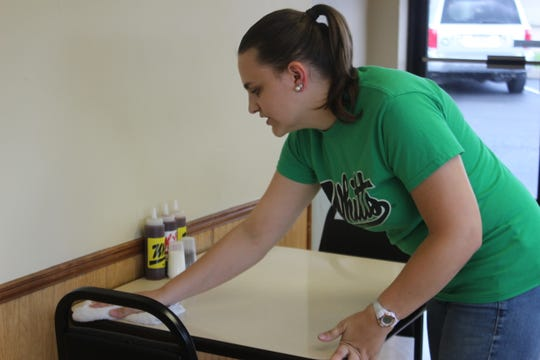 Cheyenne Plank wipes down a table at Whitt's Barbecue in Clarksville, which reopened Monday.