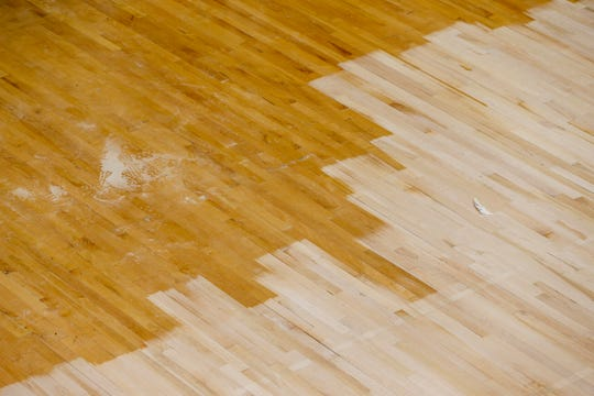 Lighter sanded spots on the basketball court are in contrast to spots unaltered at the Dunn Center on Monday, July 1, 2019.
