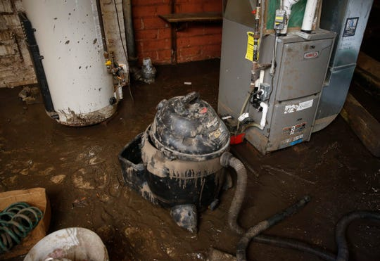 Mud cakes onto a relatively new hot water heater and furnace unit in the basement of John and Kelli Ollin's home in Des Moines on Saturday, June 29, 2019. A week earlier a flash flood caused the wall of their basement to cave in.