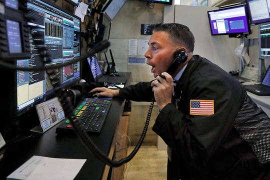 Trader Jonathan Muller works in his booth on the floor of the New York Stock Exchange, Monday, July 1, 2019. Stocks were rallying early Monday after the U.S. and China agreed to resume trade talks. (AP Photo/Richard Drew)