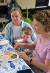 Cherille VanWinkle cuts up pancakes for grandson Nolan Grimm, 2, as Kristen Grimm looks on Monday. The two families from near Marysville, Ohio camped at the Keith Charter Traverse City State Park and were preparing to venture out to area attractions for the day.