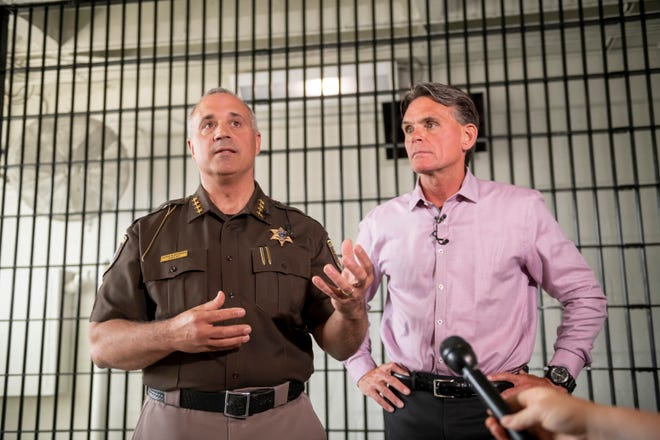 Macomb County Sheriff Anthony Wickersham, left, and Macomb County Executive Mark Hackel answer questions from the media while standing inside a jail cell inside the D block of the Macomb county jail.
