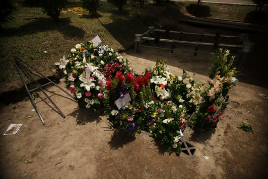 Flowers cover the grave of Oscar Alberto Martinez Ramirez and his almost two-year-old daughter Valeria inside the Municipal Cemetery of La Bermeja in San Salvador, El Salvador.