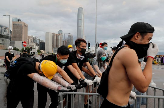 Protesters push a barrier to position as they attempt to block a ceremony in Hong Kong on Monday, July 1, 2019.