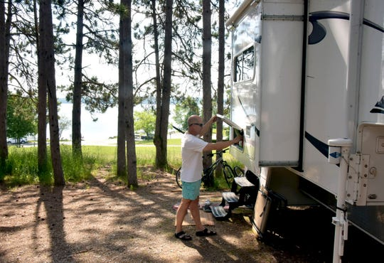 Perry Olson works on his travel trailer Monday at the Whitewater Township Park on Elk Lake. The Olson family is spending the holiday in the north, exploring, fishing and swimming.