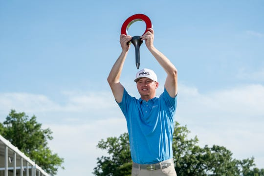 Nate Lashley holds the trophy after winning the Rocket Mortgage Classic golf tournament.