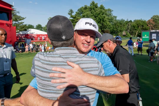 Nate Lashley receives hugs from friends and family after winning the Rocket Mortgage Classic in Detroit.