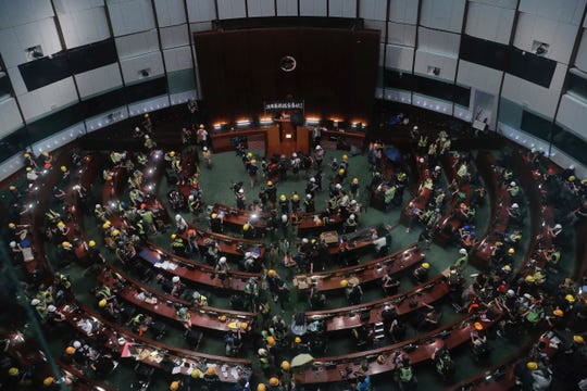 Protesters gather inside the meeting hall of the Legislative Council in Hong Kong, Monday, July 1. Protesters in Hong Kong took over the legislature's main building Friday night, tearing down portraits of legislative leaders and spray painting pro-democracy slogans on the walls of the main chamber.