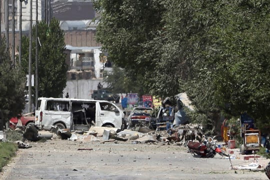 Destroyed vehicles, including a white van, sits at the site of an explosion in Kabul, Afghanistan, Monday, July 1, 2019.