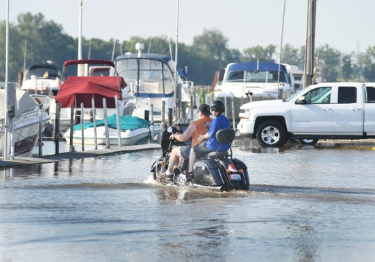 A motorcycles and passenger traverse high water on a usually dry parking lot at the Humbug Marina in Gibralter, Michigan on July 1, 2019.