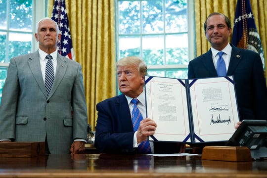 President Donald Trump, joined by Vice President Mike Pence, left, and Secretary of Health and Human Services Alex Azar, right, holds up a $4.6 billion aid package to help the federal government cope with the surge of Central American immigrants at the U.S.-Mexico border.