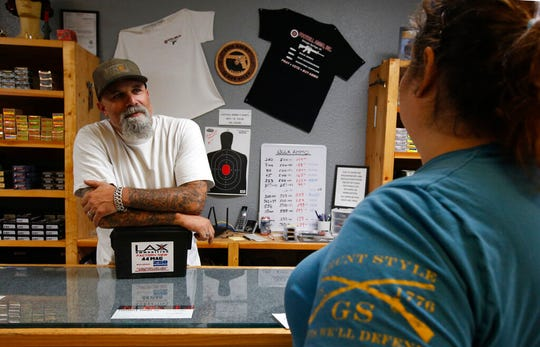 In this photo taken Tuesday, June 11, 2019, Chris Puehse, left owner of Foothill Ammo helps a customer at his shop in Shingle Springs, Calif. Californians will have to undergo criminal background checks every time they buy ammunition starting July 1 under a 2016 voter-approved ballot initiative.