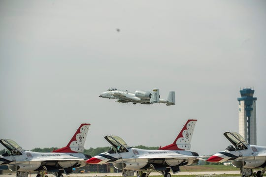 A resident 122nd Fighter Wing Air Force A-10C Super Sabre flies over the line of Air Force Thunderbird F16s during the 2019 Fort Wayne Air Show.