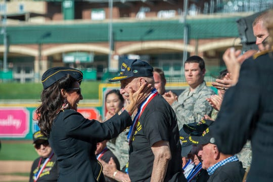 A medal and a kiss from one of the Ladies for Liberty to a WWII veteran honored at the Fort Wayne Air Show Welcome Party on the 75th anniversary of the D-Day Invasion of France by Allied Forces.