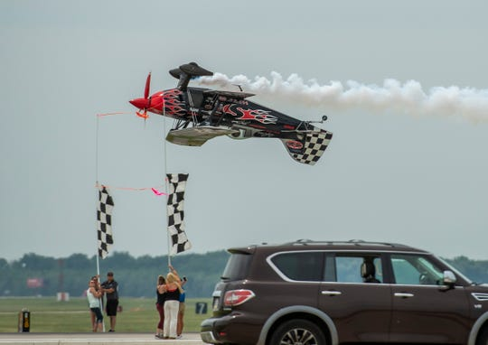Acrobatic pilot Skip Stewart cuts the tape held between two uprights while flying upside down during the 2019 Fort Wayne Air Show.