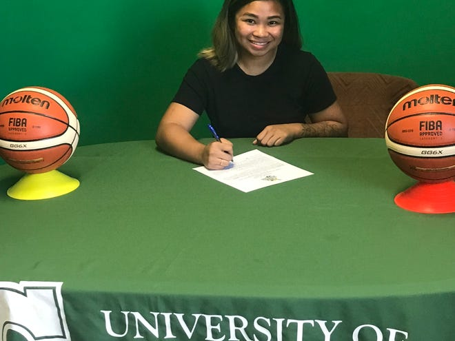 Shania Bulala signs with the University of Guam's women's basketball team.