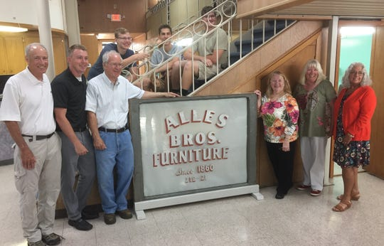 Alles Brothers Furniture owners and employees gather around an old sign that hung over the transom as the store prepared to reopen Monday morning after being closed for nine months. The store marks its 120th anniversary this year.