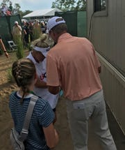Steve Stricker checks scorecard with caddie/wife Nicki as 13-year-old daughter Izzy looks on after his U.S. Senior Open win at Notre Dame's Warren Golf Course