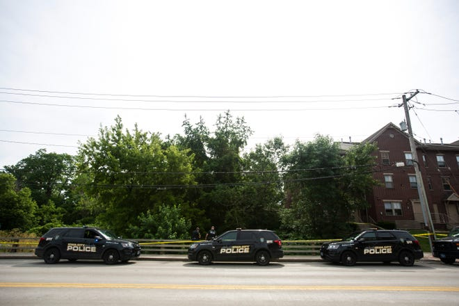 Iowa City police officers look down towards the creek while responding to a scene, Monday, July 1, 2019, in the 400 block of South Gilbert Street at Ralston Creek in Iowa City, Iowa.