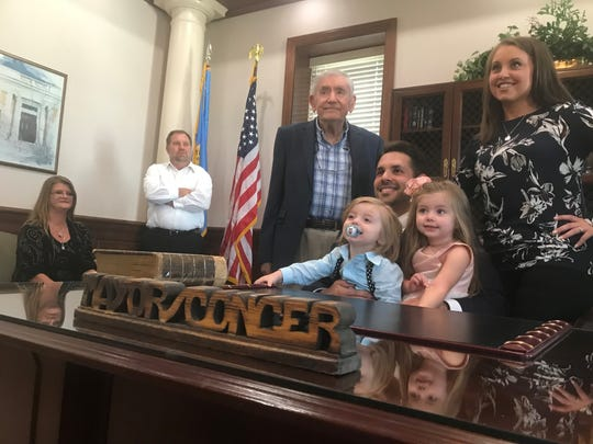 "Jackson Mayor Scott Conger found the desk decoration that reads ""MAYOR CONGER"" that belonged to his grandfather, former Jackson Mayor Bob Conger, while going through things in the basement at his grandmother, Virginia's, house last week. Conger and his family — wife Nikki and children Madelynn and Charlie — take a picture with Conger's uncle, Norwood Jones."