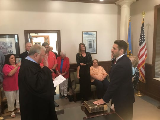 Jackson City Judge Blake Anderson, left, swears in new Jackson Mayor Scott Conger during a private ceremony at City Hall on Monday, July 1, 2019.