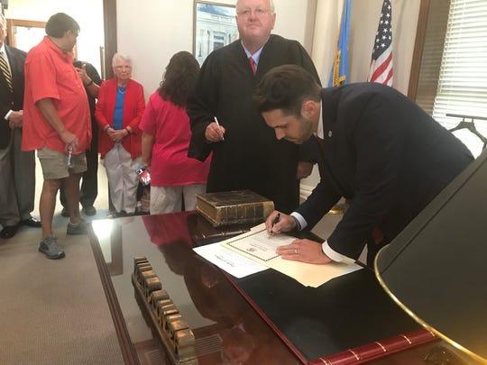 Jackson Mayor Scott Conger signs documents formalizing his inauguration at mayor on Monday, July 1, 2019.