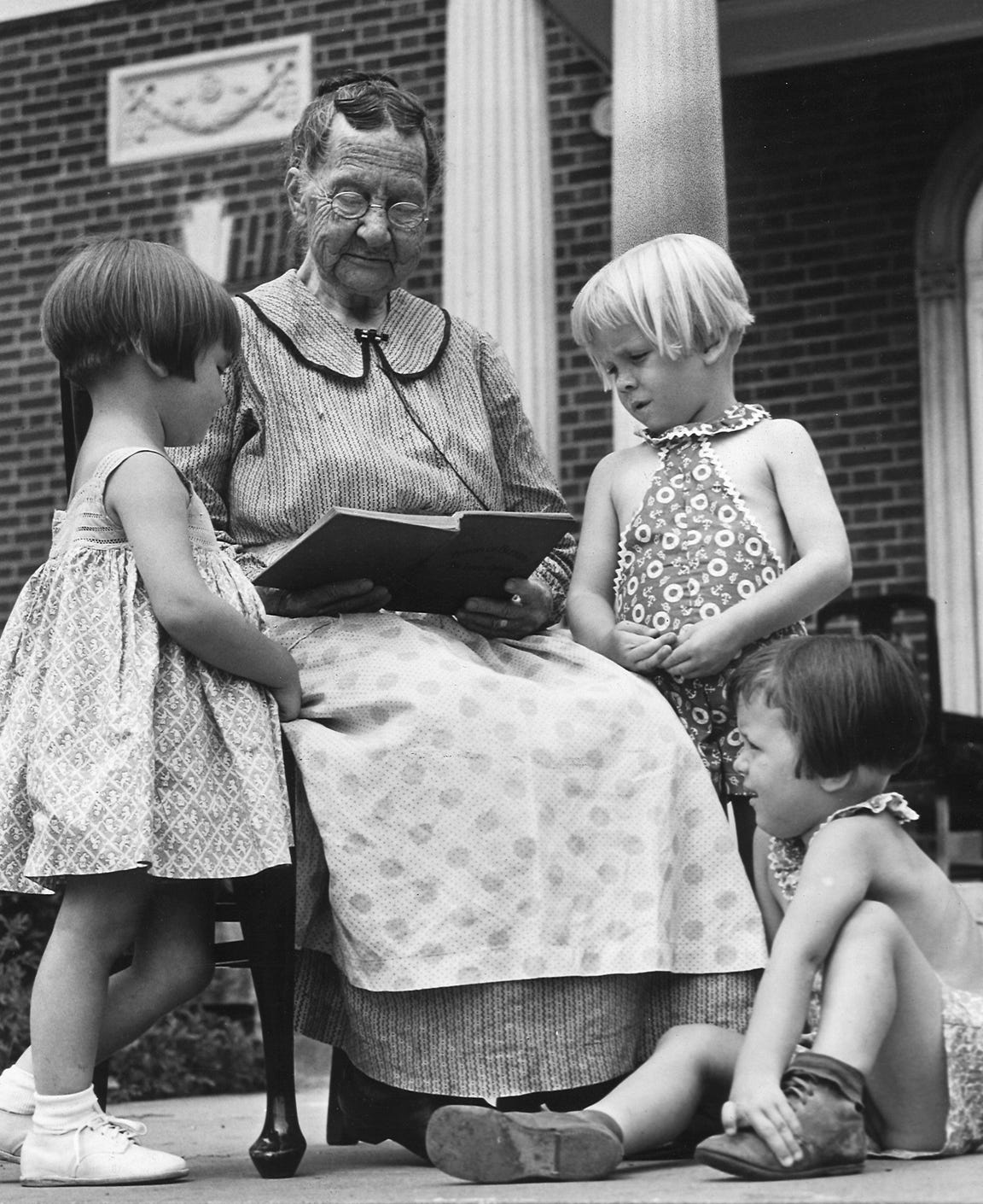 Elizabeth Richardson, 85, Masonic Homes' oldest widow, reads to Laura Brown, 3, left, and Ruby and Ruth Sowder, 4.