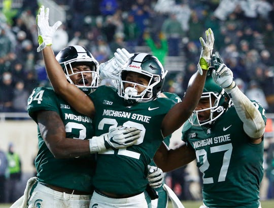 Cornerback Josiah Scott #22 celebrates with linebacker Antjuan Simmons #34 and safety Khari Willis #27 of the Michigan State Spartans after intercepting a pass by quarterback Giovanni Rescigno #17 of the Rutgers Scarlet Knights during the fourth quarter at Spartan Stadium on November 24, 2018 in East Lansing, Michigan. Michigan State defeated Rutgers 14-10.