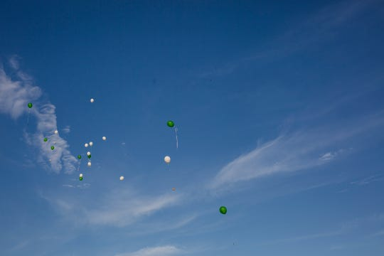 Balloons float off into the sky after being released by the attendees of the event.