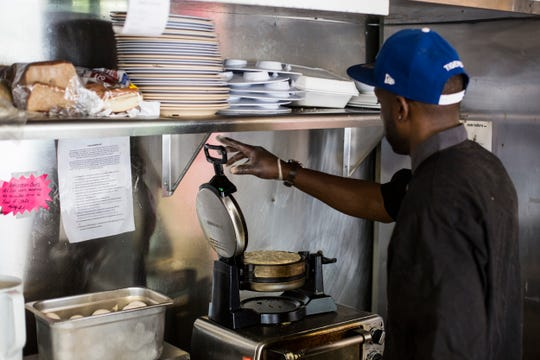 Trashaun Davis cooks up a waffle while working at The Waffle Iron at 4969 Park Ave. on July 1, 2019. After a fire at the original location in Collierville, The Waffle Iron has reopened in East Memphis.