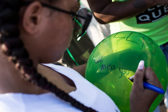 Jayla Mariee writes on a balloon before releasing it during a healing circle event in Frayser organized by the Black Lives Matter Memphis chapter for Brandon Webber.
