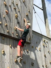 Scout Grayson Jones breaking a climbing wall record while earning his Climbing Merit Badge.