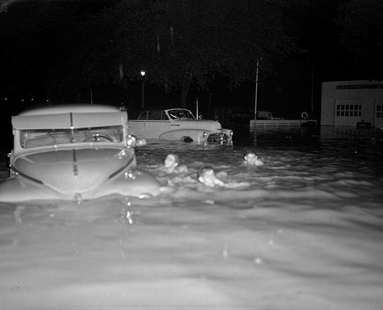 Three boys go for a late-night swim after the intersection of North 20th Street and West Capitol Drive is turned into a lake, thanks to a  storm bringing 5 inches of rain and subsequent sewer backups to Milwaukee on July 27, 1949. The storm swamped the northern half of the Milwaukee area; three people were electrocuted by a downed power line. This photo was on the front page of the July 28, 1949, Milwaukee Journal.
