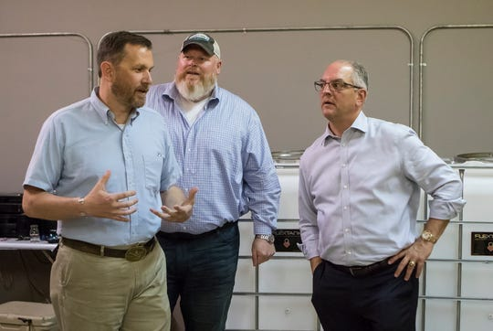 Co-owners Curtis Sims, left, and Cameron Myers give La. Gov. John Bel Edwards a tour of the site for Two Warriors Meadery in West Monroe, La. on July 1.