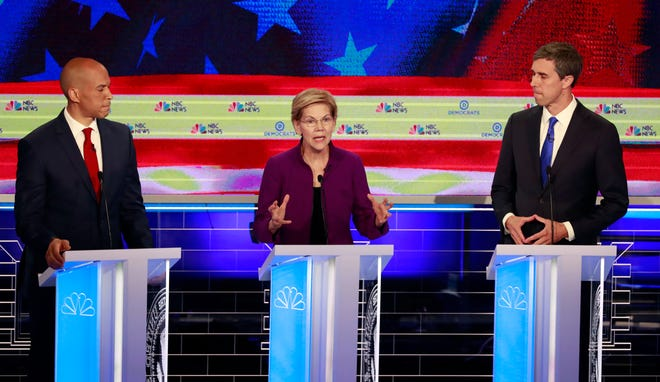 Democratic presidential candidate U.S. Sen. Elizabeth Warren, D-Mass., speaks during a Democratic primary debate hosted by NBC News at the Adrienne Arsht Center for the Performing Arts on Wednesday, June 26, 2019, in Miami, as U.S. Sen. Cory Booker , D-N.J., and former El Paso U.S. Rep. Beto O'Rourke listen.