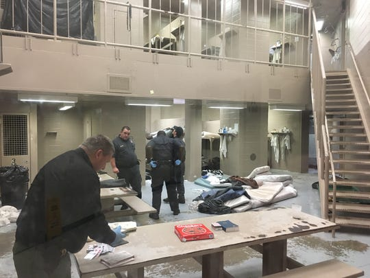 Officers search a cell block in the Autauga Metro Jail on Monday morning.