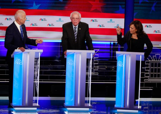 Democratic presidential candidate former Vice President Joe Biden, left, and U.S. Sen. Kamala Harris, D-Calif., spar during the Democratic primary debate hosted by NBC News at the Adrienne Arsht Center for the Performing Arts on Thursday, June 27, 2019, in Miami. Sen. Bernie Sanders, I-Vt., is in the center.