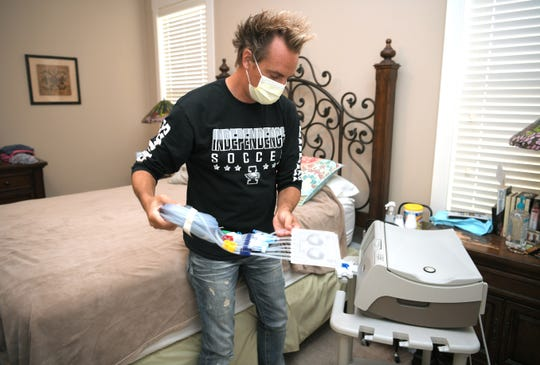 Former Independence High teacher and boys' soccer coach and now Brentwood Middle Assistant Principal Josh Phillips prepares for dialysis treatment at his home in Thompson Station. Heexperienced kidney failure last July. He is getting a kidney transplant in August from his brother.