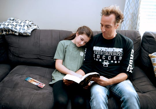 Former Independence High teacher and current Brentwood Middle Assistant Principal Josh Phillips and his daugher Maddie read 'Lord of the Rings' together at their Thompson Station home on Saturday, June 29, 2019. Phillips experienced kidney failure last July. He is getting a kidney transplant in August from his brother.