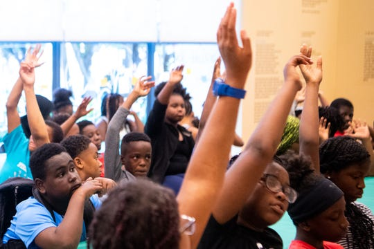Children raise their hands while talking about current events during the Nashville Public Library's summer program at the library Thursday, June 20, 2019, in Nashville, Tenn.