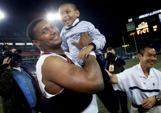 Tennessee Titans quarterback Steve McNair smiles as he lifts his son Tyler after defeating the New England Patriots 24-7 at the Nashville Coliseum Dec. 16, 2002.