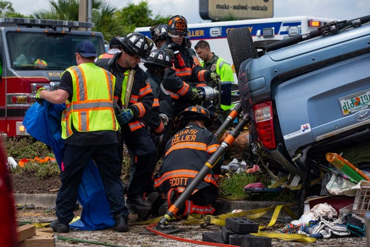 Emergency personnel work to free a person involved in a rollover Monday, July 1, 2019, at the 12300 block of U.S 41 in North Naples.