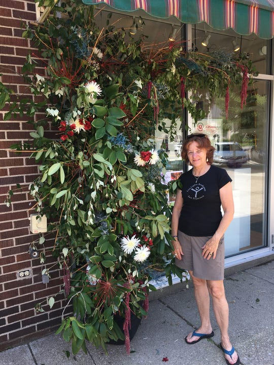 "Granville's Evelyn Frolking, ""eco-conscious floral artisan,"" with her completed display."